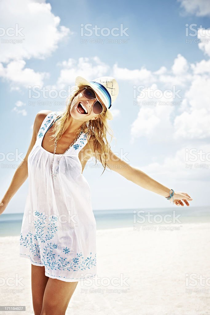 Cheerful woman with arms out enjoying at beach royalty-free stock photo