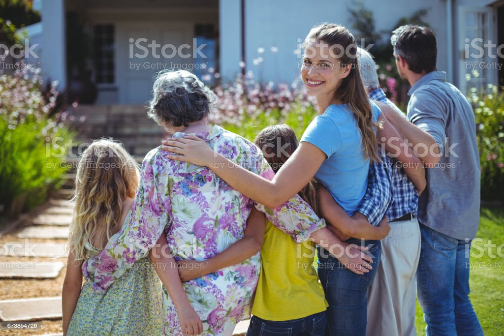 Cheerful woman with family in back yard stock photo