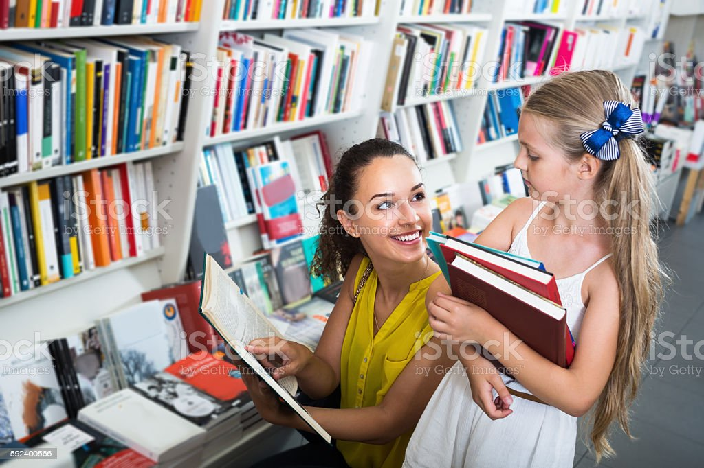 Cheerful woman with girl looking in open book stock photo