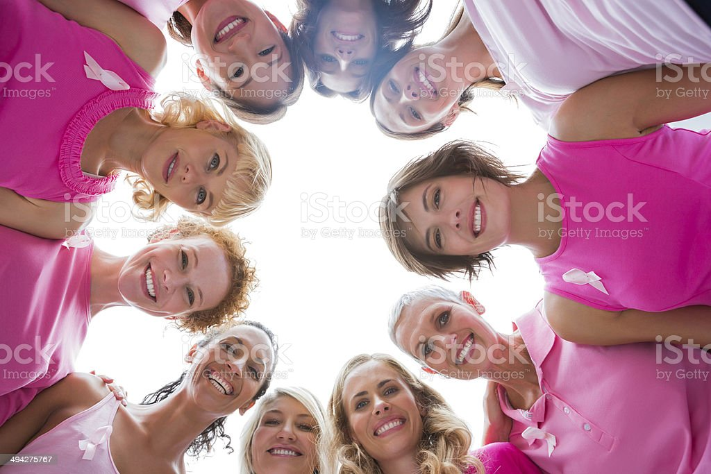 Cheerful women in circle wearing pink for breast cancer stock photo