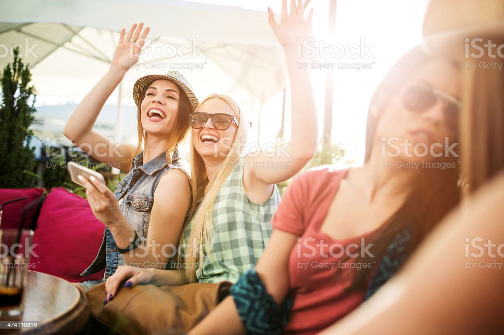 Cheerful women waving to someone in a cafe. stock photo