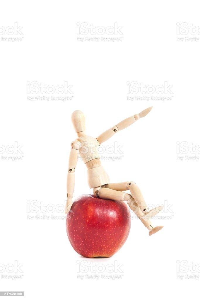cheerful wooden doll sitting on apple stock photo