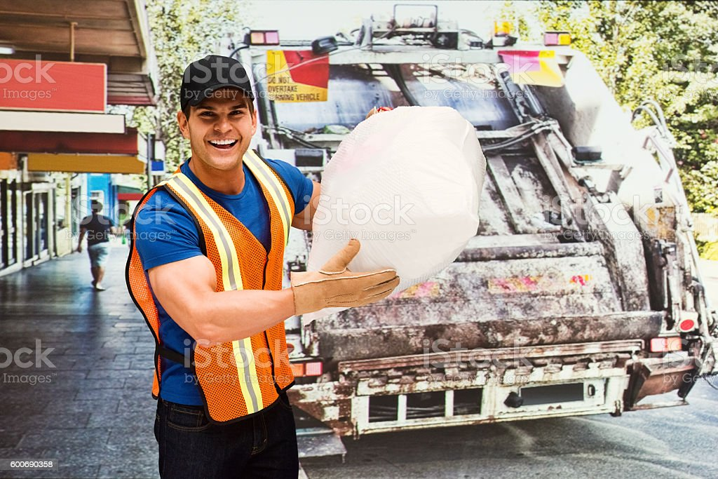 Cheerful worker holding garbage bag stock photo
