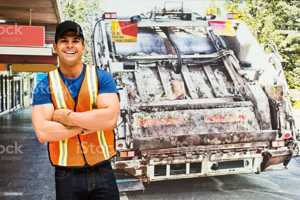 Cheerful worker standing in front of garbage can stock photo
