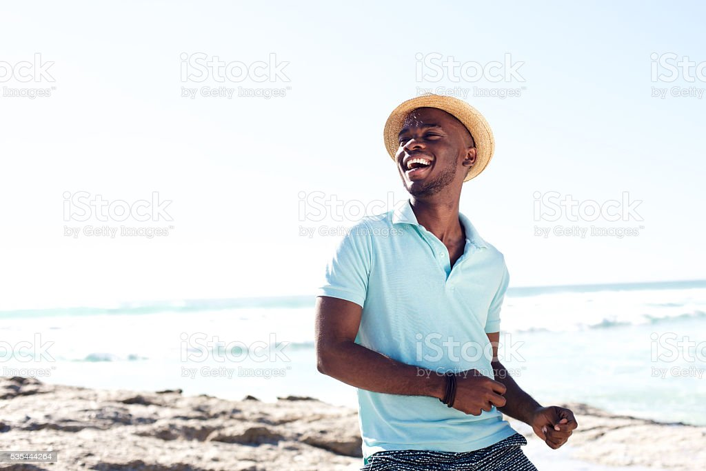 Cheerful young african man enjoying at the beach stock photo