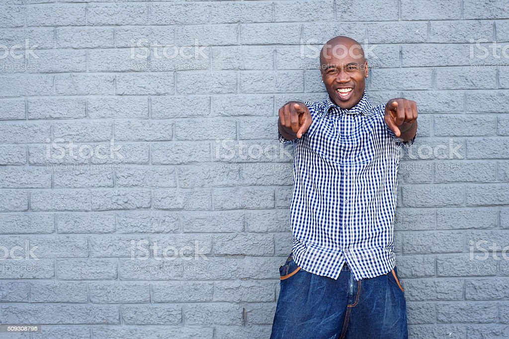 Cheerful young african man pointing finger stock photo