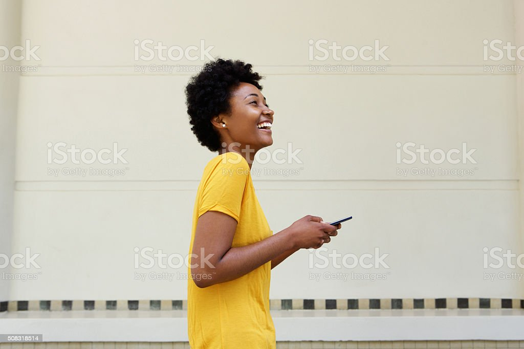 Cheerful young african woman walking with a mobile phone stock photo