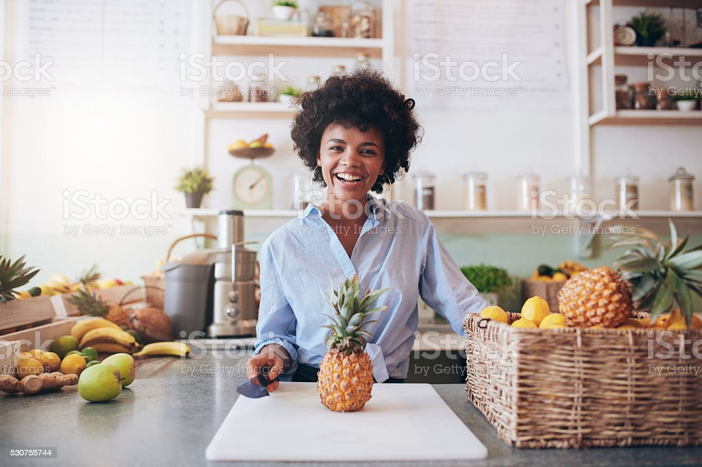 Cheerful young african woman working at juice bar stock photo