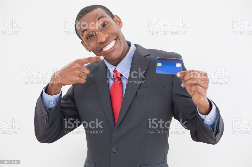 Cheerful young Afro businessman pointing at credit card stock photo