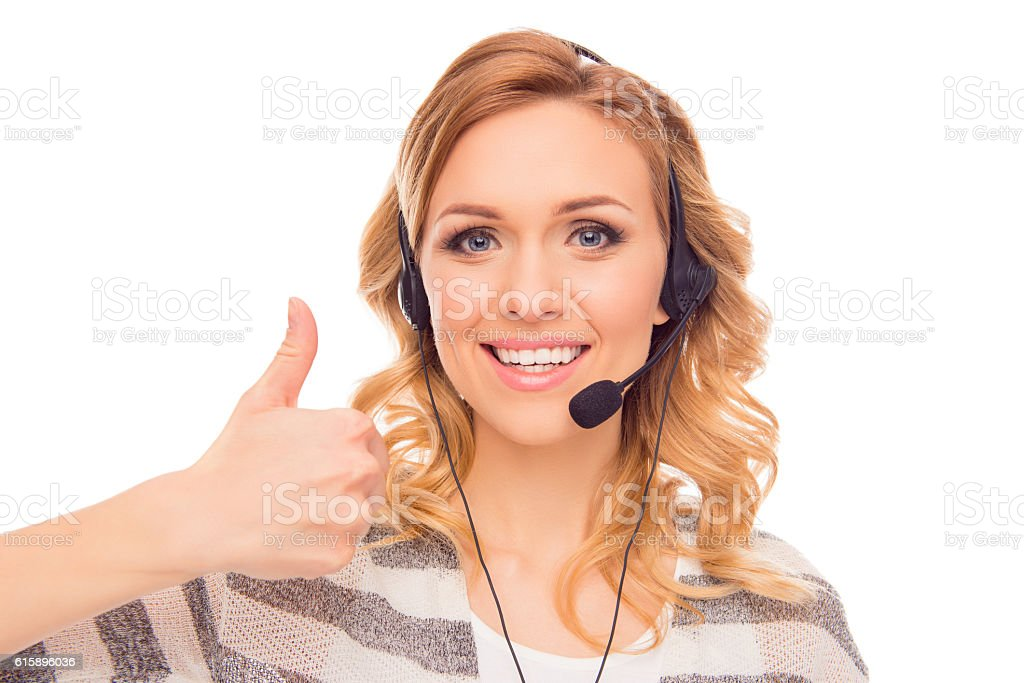 Cheerful young agent of call center showing thumb up stock photo