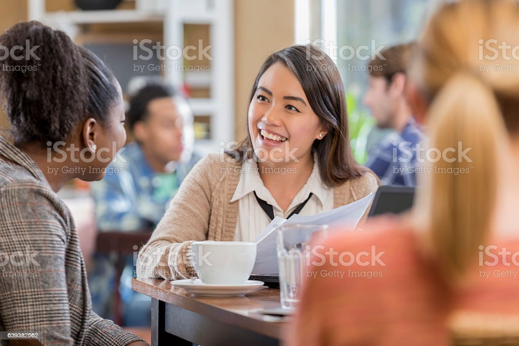 Cheerful young Asian woman meets with colleague stock photo