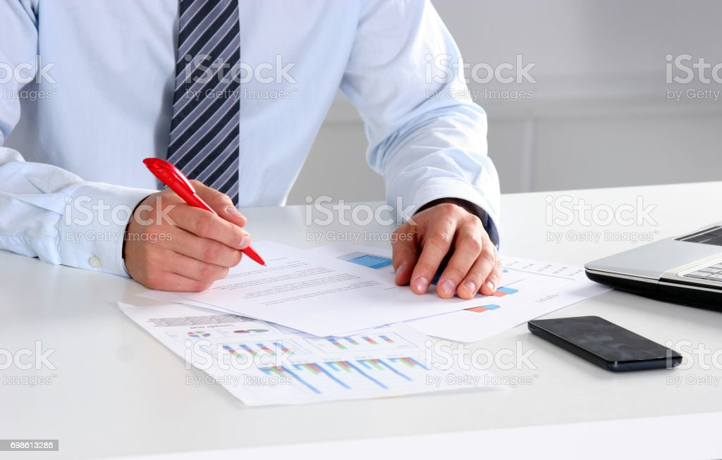 Cheerful young businessman sitting at the table in the office with laptop and looks at documents stock photo
