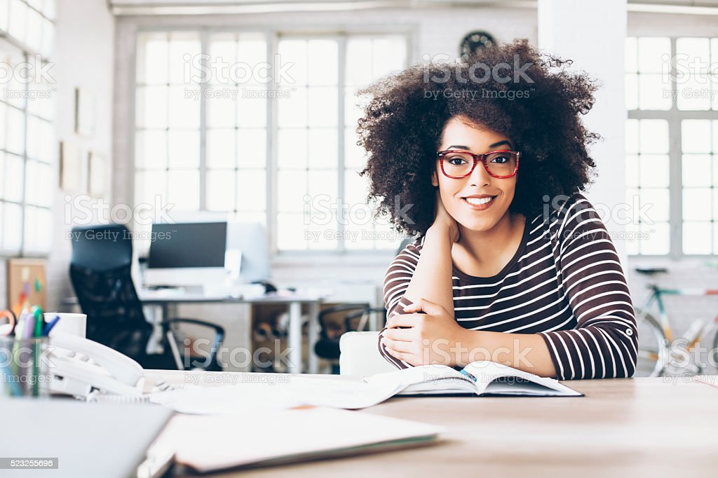 Cheerful young businesswoman sitting on desk stock photo