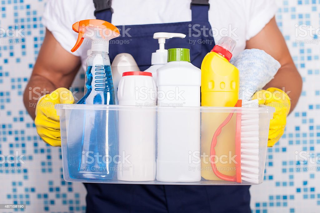 Cheerful young cleaner is presenting his equipment stock photo
