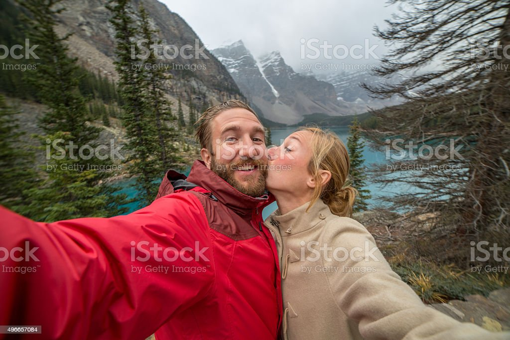 Cheerful young couple at Moraine lake taking a selfie portrait stock photo