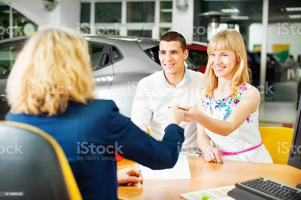 Cheerful Young Couple Buying Car royalty-free stock photo