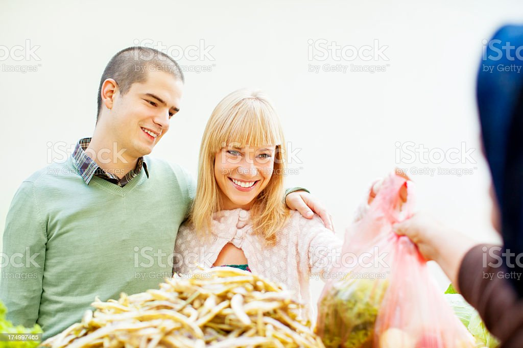 Cheerful Young Couple buying organic vegetable. royalty-free stock photo