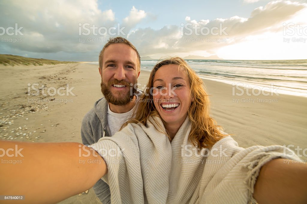 Cheerful young couple by the sea take a selfie portrait stock photo