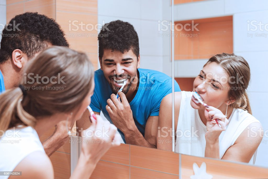 Cheerful young couple cleaning teeth together stock photo