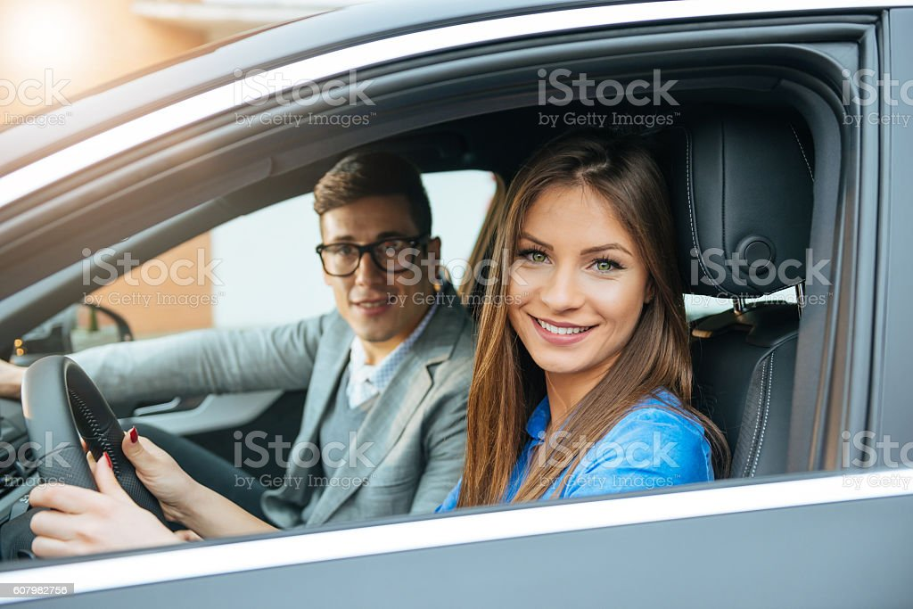 Cheerful young couple driving luxury car and traveling for holiday stock photo