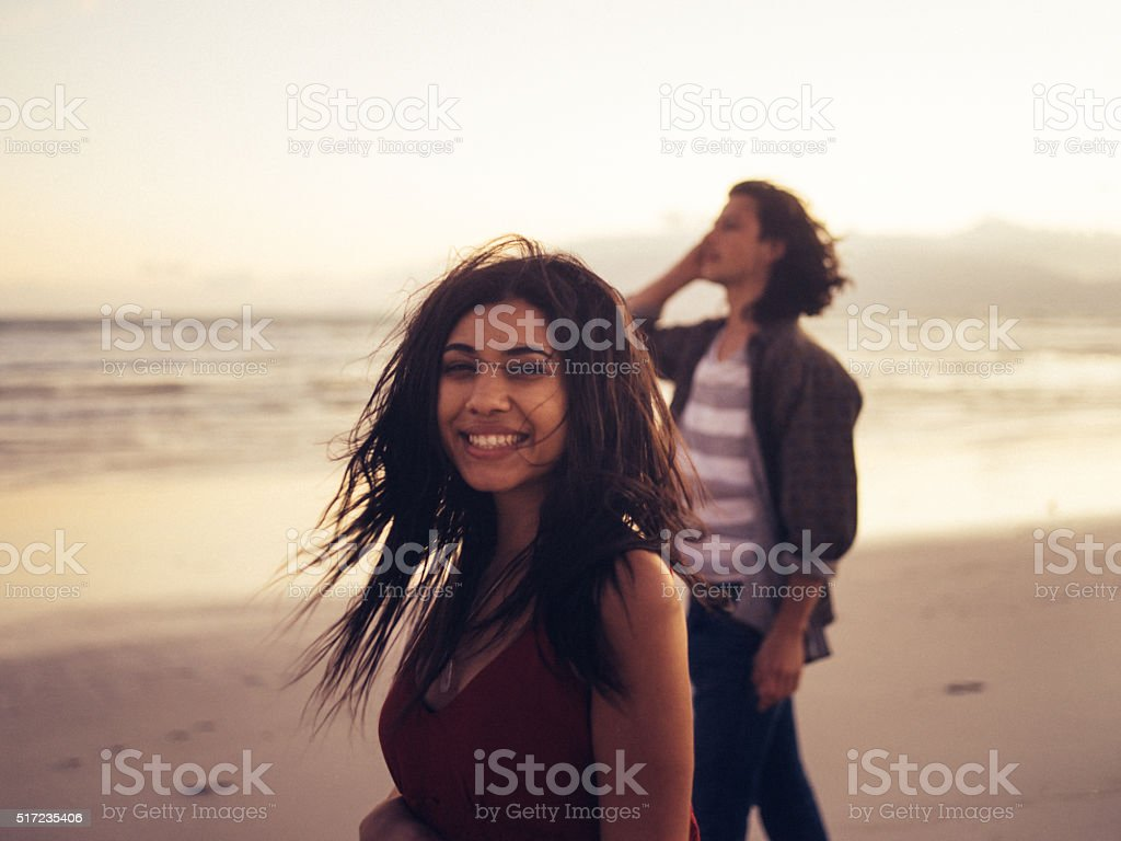 Cheerful young couple enjoying the beach at sunset stock photo