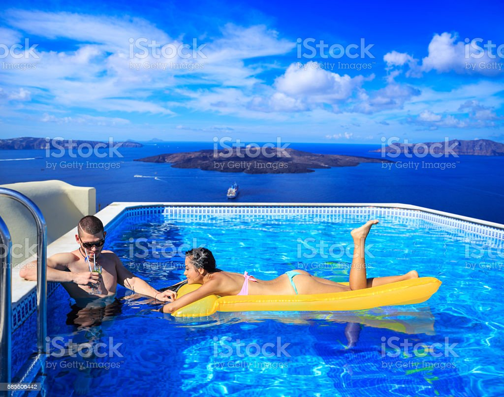 Cheerful young couple having fun at swimming pool stock photo