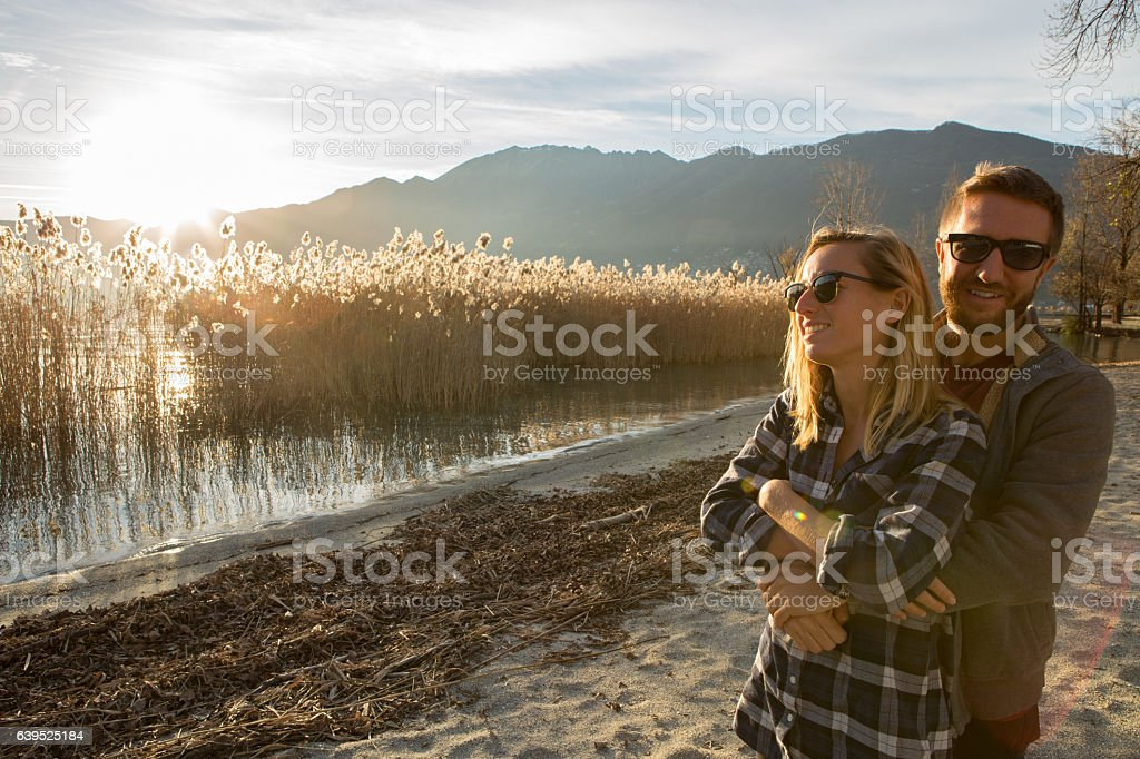 Cheerful young couple hugging by the lakeshore at sunset stock photo