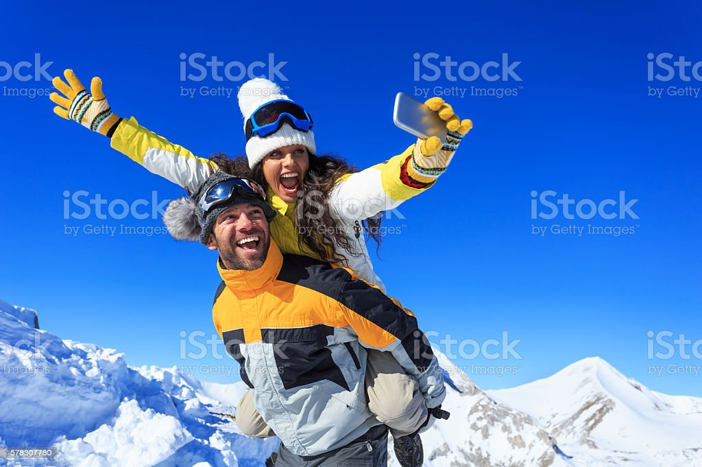 Cheerful young couple making winter selfie stock photo