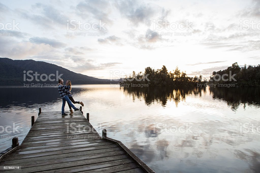 Cheerful young couple on a lake pier being affectionate stock photo