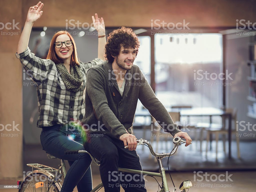 Cheerful young couple on a tandem bicycle indoors. stock photo