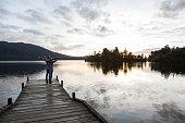 Cheerful young couple on lake pier enjoying freedom