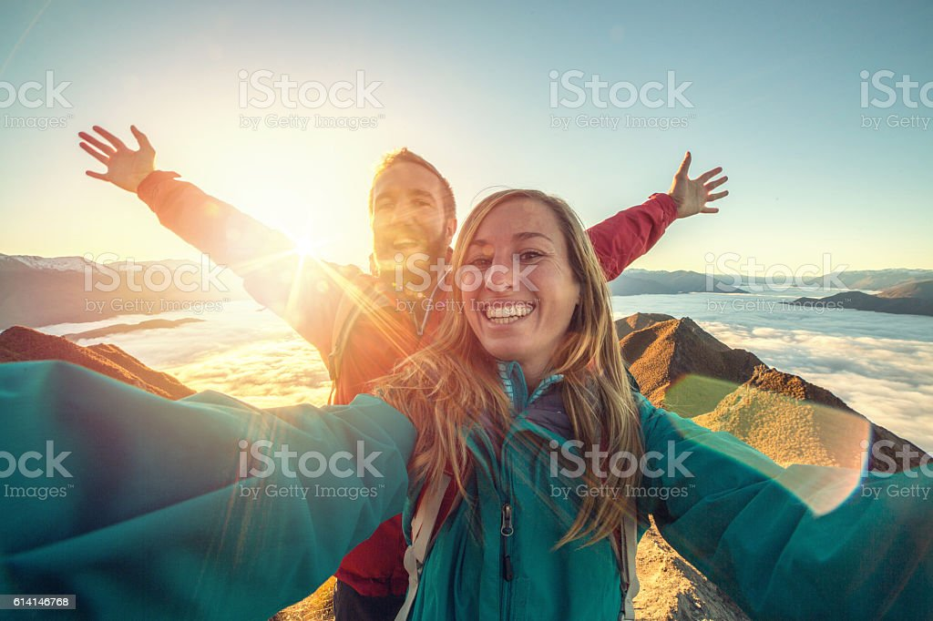 Cheerful young couple on mountain top take selfie stock photo