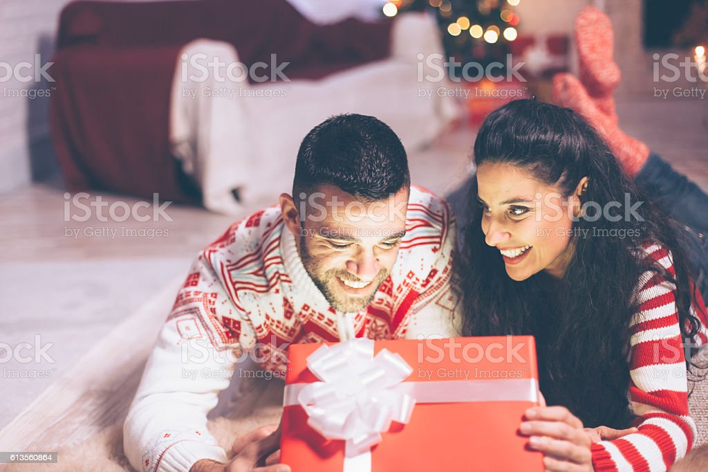 Cheerful young couple opening christmas present stock photo