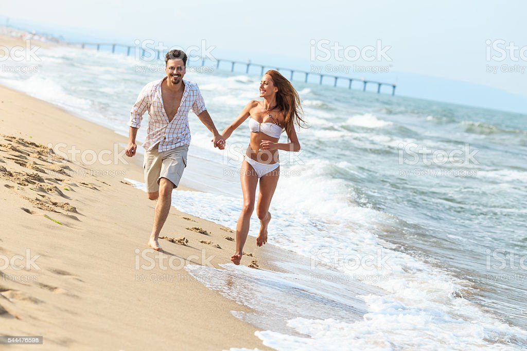 Cheerful young couple running on beach stock photo