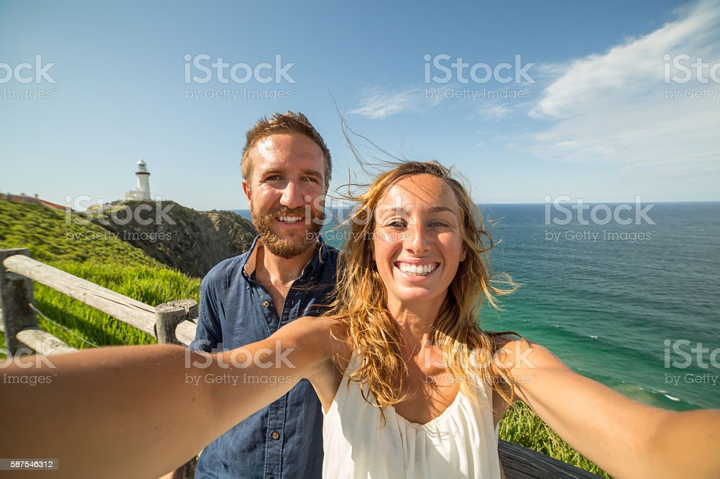 Cheerful young couple take a selfie portrait at Cape Byron stock photo