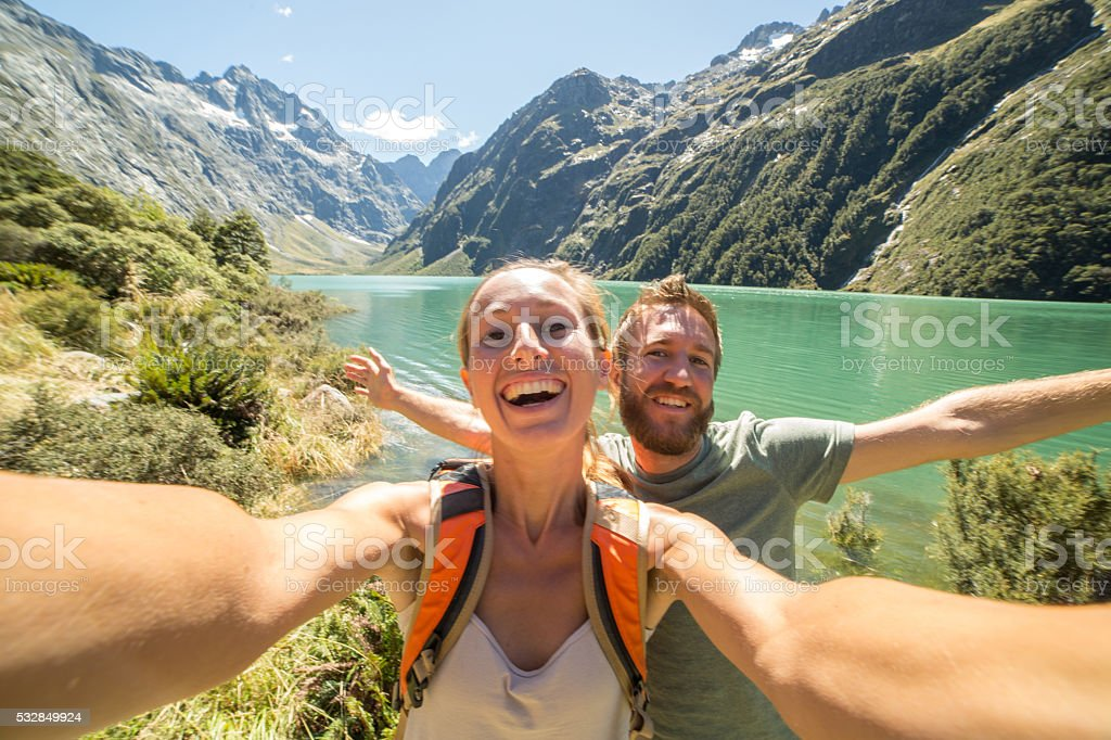 Cheerful young couple take a selfie portrait by the lake stock photo