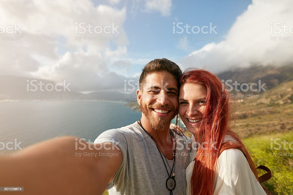 Cheerful young couple taking a selfie stock photo