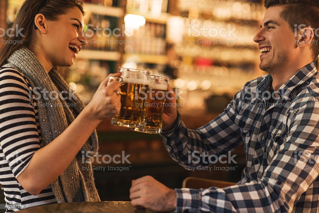 Cheerful young couple toasting with beer in a bar. stock photo
