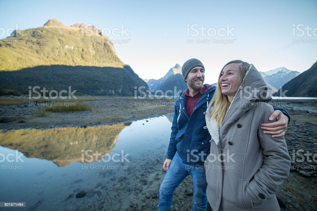 Cheerful young couple walking by the lake shore stock photo