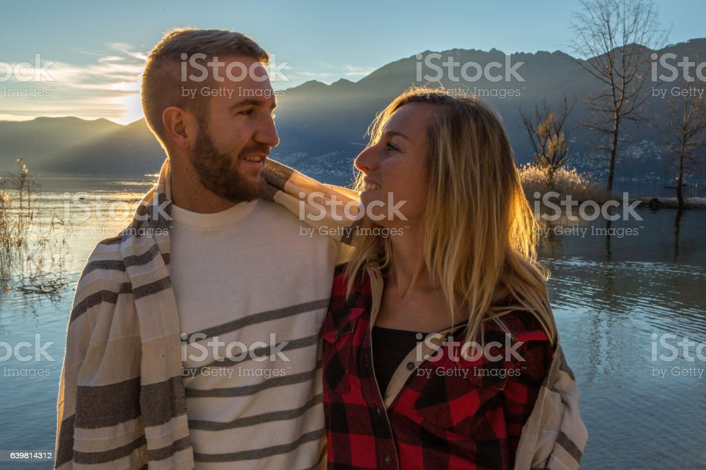 Cheerful young couple wrapped in blanket by the lakes, sunset stock photo