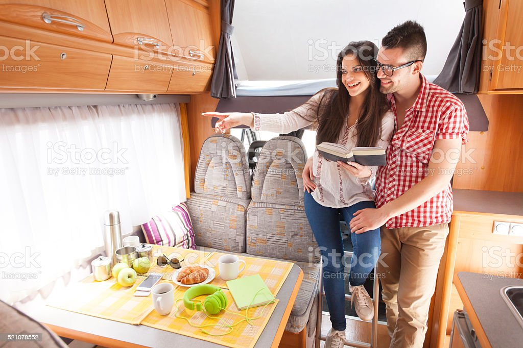 Cheerful young couplehaving fun inside of a camper stock photo
