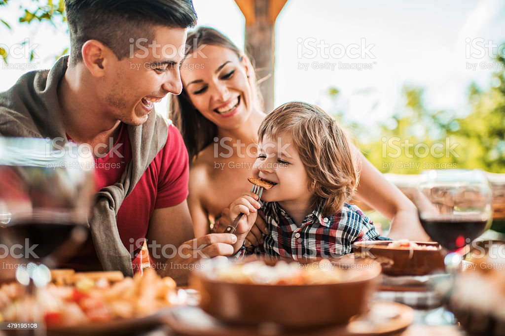 Cheerful young father feeding his son in restaurant. stock photo