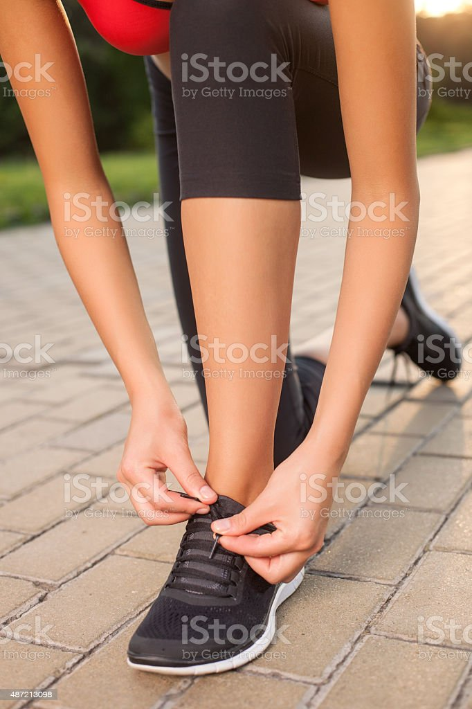 Cheerful young female athlete is preparing for jogging stock photo