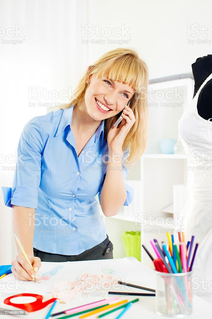 Cheerful Young Female Dressmaker Talking on the phone. royalty-free stock photo