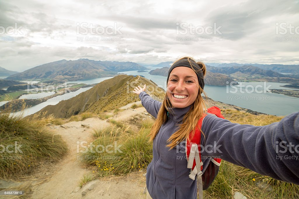 Cheerful young female takes self portrait on mountain top stock photo