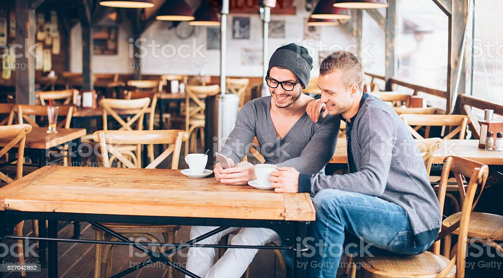 Cheerful young friends drinking coffee in a bar stock photo