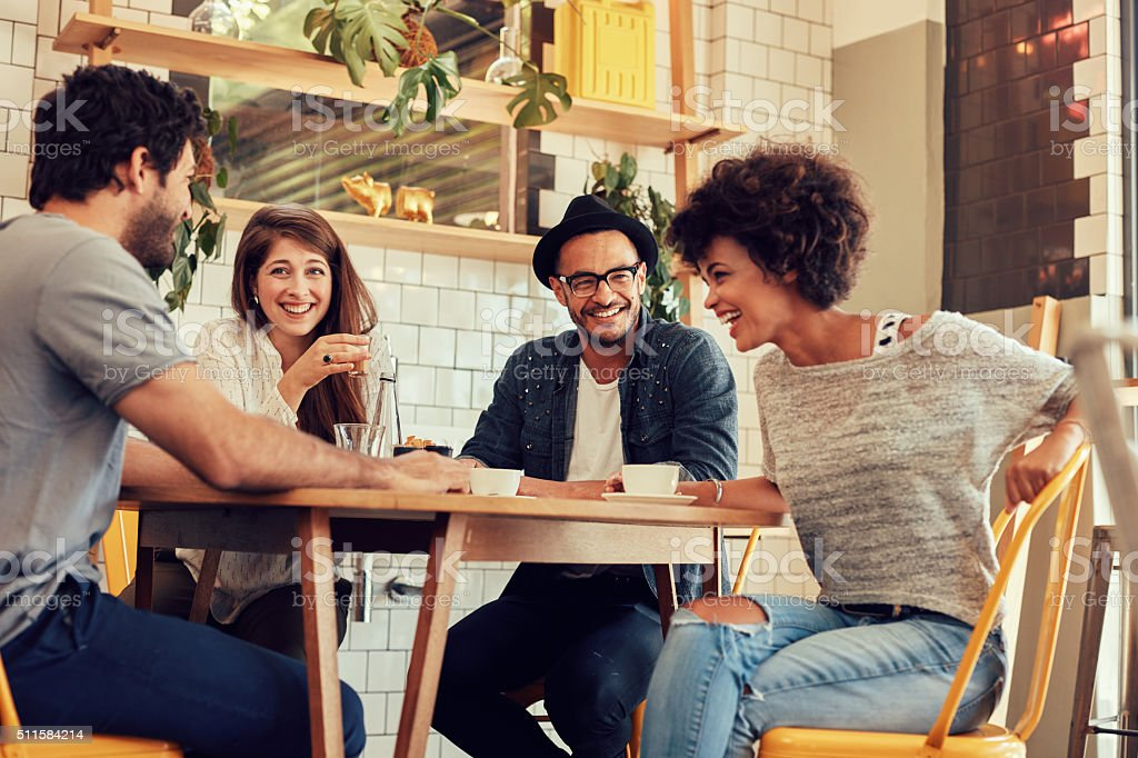 Cheerful young friends having fun in a cafe stock photo