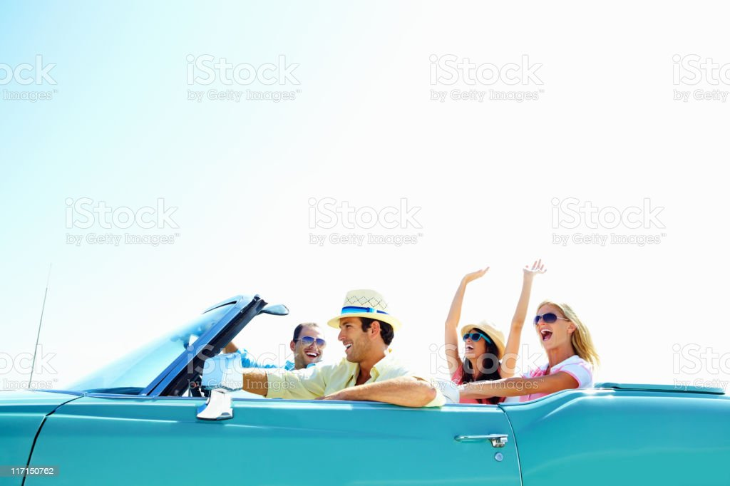 Cheerful young friends in a car on vacation trip stock photo