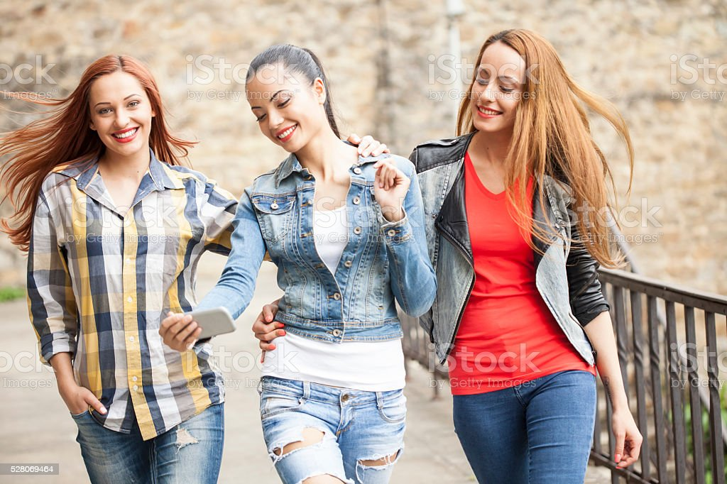 Cheerful young friends walking together in the city stock photo