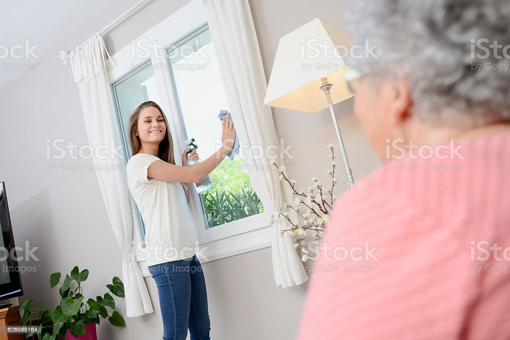 cheerful young girl helping with household chores elderly woman home stock photo